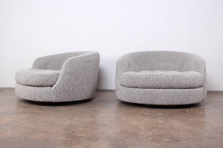 A pair of oversized swivel chairs on walnut bases newly upholstered in Maharam pebble wool. Designed by Milo Baughman for Thayer Coggin.