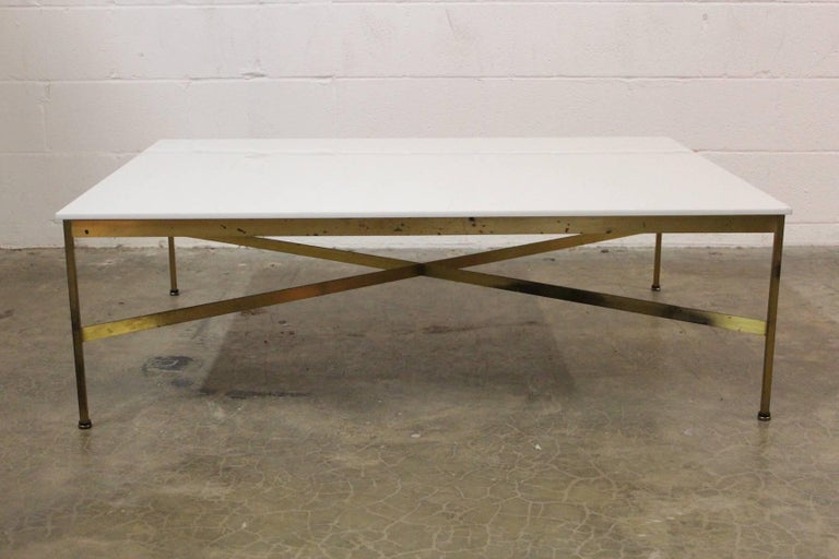 A large patinated brass coffee table with Vitrolite white glass top. Designed by Paul McCobb for Calvin.