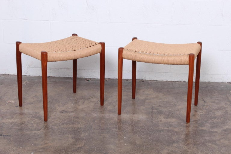 A pair of teak stools with paper cord seats. Designed by Niels O. Møller, manufactured by J.L. Møllers Møbelfabrik.