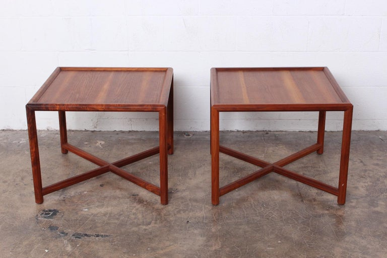 A pair of walnut Janus end tables designed by Edward Wormley for Dunbar.