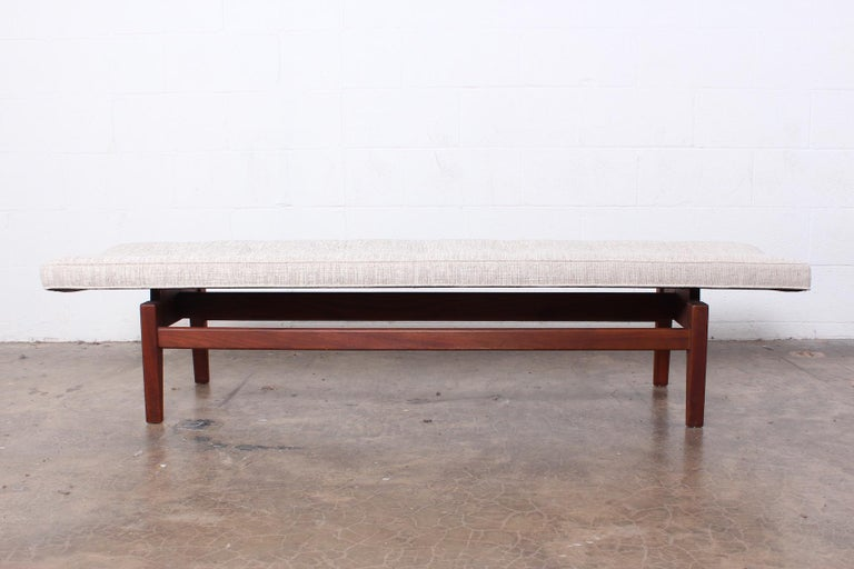 A large curved top bench with walnut base. Designed by Jens Risom.