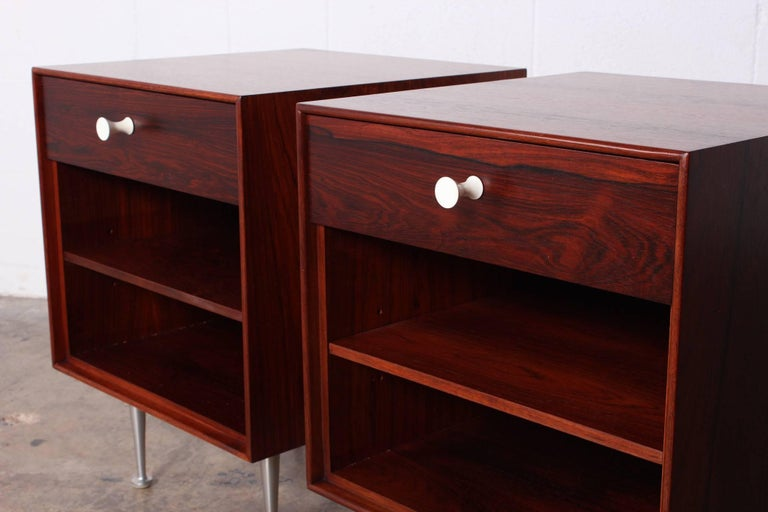 A pair of rosewood thin edge nightstands with aluminium legs and porcelain pulls. Each with adjustable rosewood shelf. Stamped