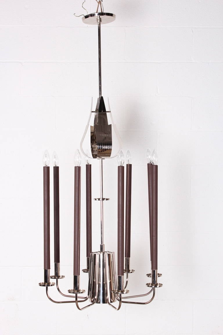 A rare and large design for Parzinger Originals. This model has eight leather wrapped candelabras and a larger down light with perforations in the central cone.