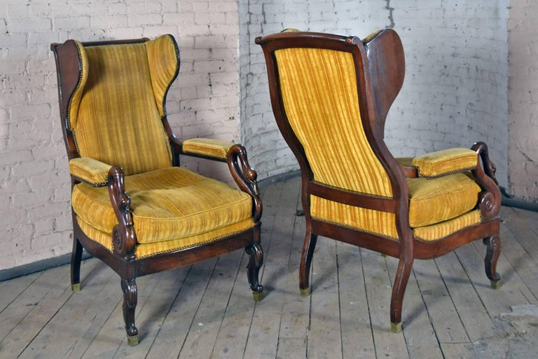 Exceptional pair of late Empire period chairs, of comfortable size and flowing movement of form. The accentuated wings beautifully complementing the wavy movement of the back and back legs, the arms ending in scrolling swan's necks, the front legs