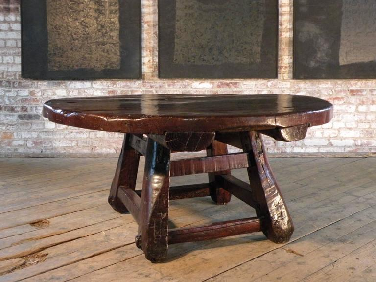 Unusual, striking, bold. Large low round table with a massive top supported by a flared square base constructed from roughly hewn wooden beams.