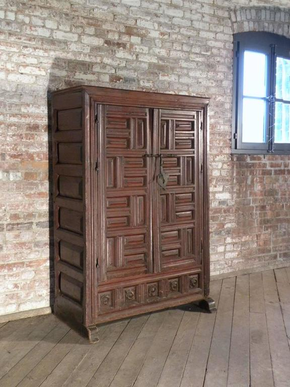 Small two-door wardrobe with an interesting conceptual look. The geometrically paneled and molded doors with an iron bolted lock opening to an interior featuring a top shelf above a hanging rod. The later green painted interior contrasting