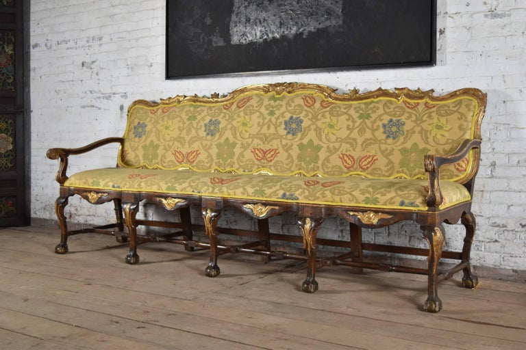 Exceptional, long open arm walnut sofa with carved and gilt accents, the cabriole legs ending in ball and claw feet and joined by stretchers.