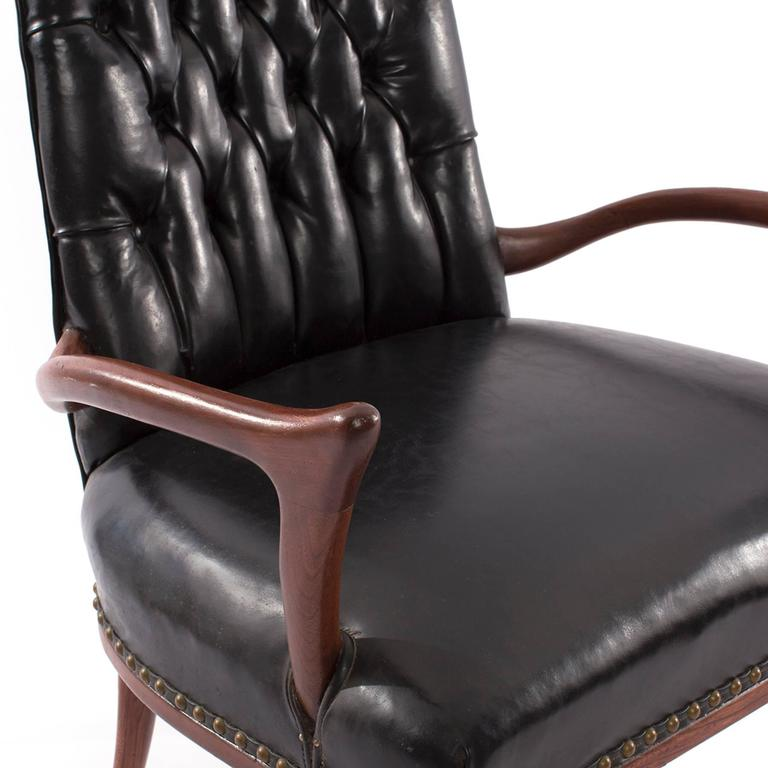 Sculptural mahogany and upholstered arm chair circa late 1950's. This all original example has stunning flared arms and legs and original black vinyl and brass tack upholstery. Can easily be upholstered in a leather or fabric of your choice.