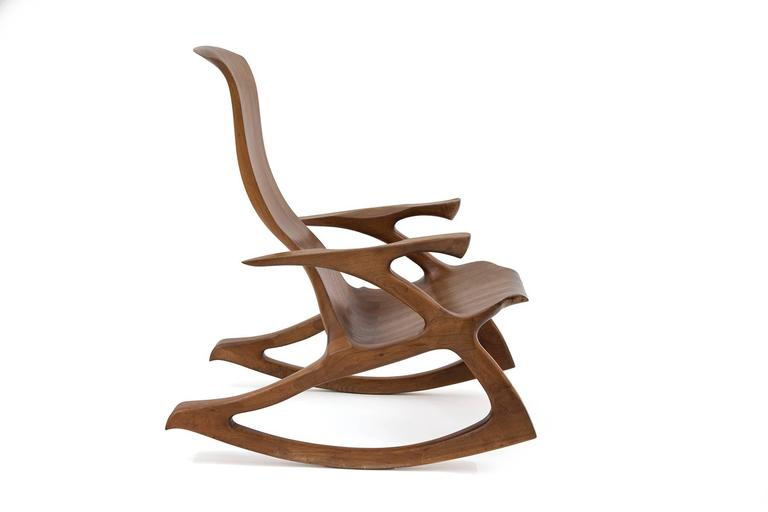 Solid walnut studio crafted rocking chair. This example has sculpted arms and frame with inset dove tailing and subtly curved back. Looks incredible from every angle.