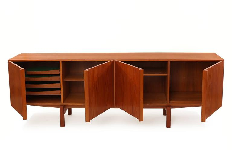 Ib Kofod-Larsen teak sideboard or credenza circa late 1960s. This all original example has Larsen's ingenious leg detail that extends into the handles of the doors. The interior of the chest has four drawers and adjustable shelves. Case and door