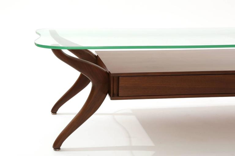 Free-form walnut and glass coffee table circa late 1950s. This example has solid walnut legs, two drawers for storage and free-form original glass top.