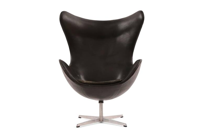 Arne Jacobsen for Fritz Hansen first generation leather egg chair, circa late 1950s. This example has beautifully patinated black leather black leather upholstery and can be used with or without the seat cushion. Has some internal drying to the foam
