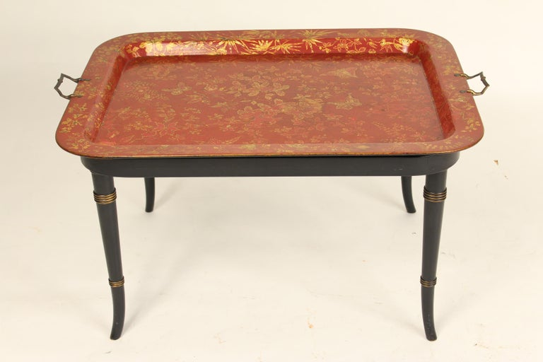 English Regency style red papier mâché and gilt decorated tray with brass handles, late 19th century, resting on a 20th century stand. The bottom of the papier mâché tray is marked