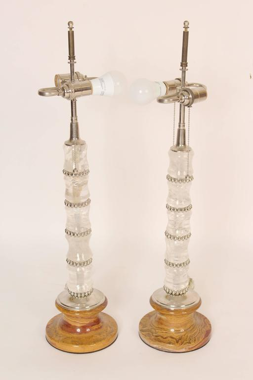 Pair of spool turned rock crystal and marble table lamps with polished nickel hardware, circa 2000. The height from the marble base to the beginning of the electrical fitting is 19