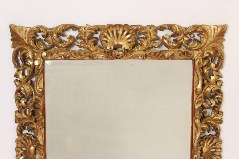 Antique Baroque style giltwood mirror having deep carved shell and foliate carvings with a bevelled glass mirror, 19th century.