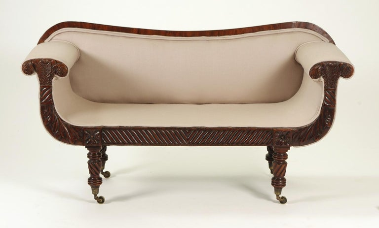 Regency mahogany child's sofa, the serpentine top rail over the upholstered seat and back; the mushroom arms with Prince of Wales feathers and acanthus leaves raised on turned legs headed by carved rosettes and ending with brass casters, joined by a