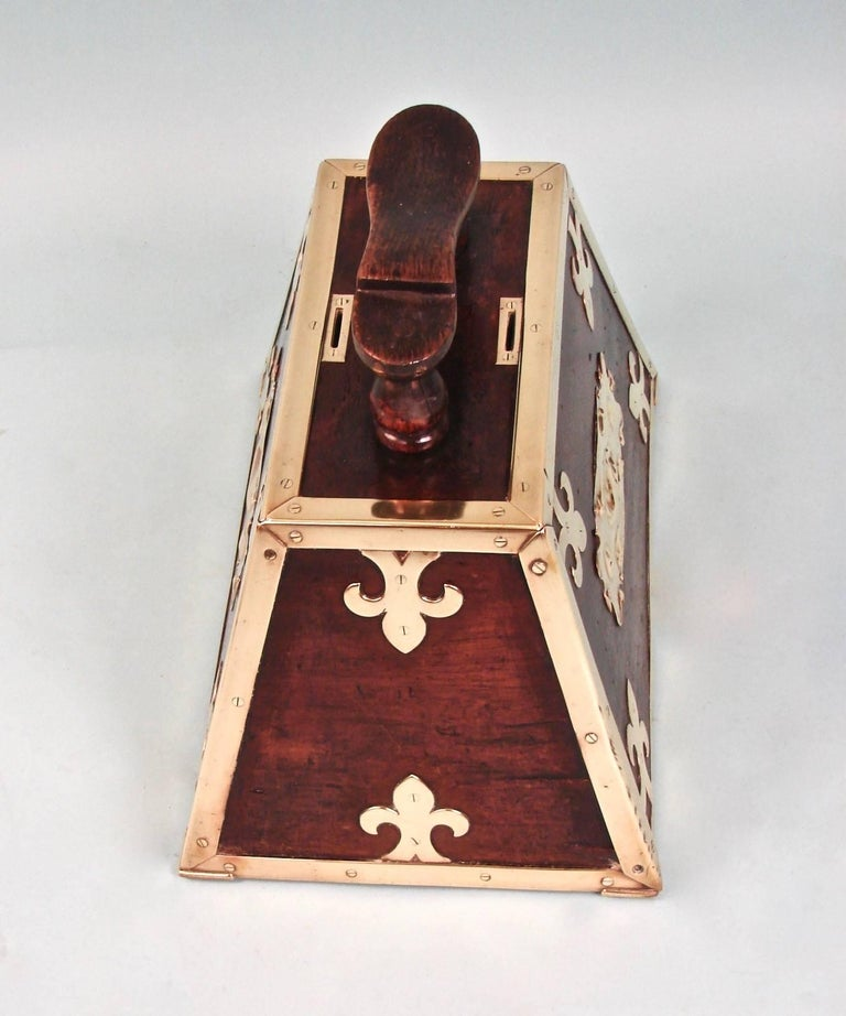 A wonderful Turkish brass-mounted mahogany Art Nouveau period shoe shine box of trapezoidal form. This is a fine example of a street vendor's original shoe shine kit with top mounted coin slots and a locking door.