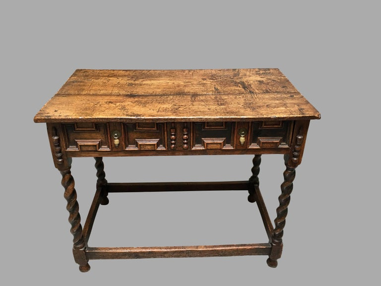 A James II period oak side table, the overhanging top above a long frieze drawer with panelled decoration, supported on barley twist legs joined by a box stretcher ending in bulb feet, circa 1680.