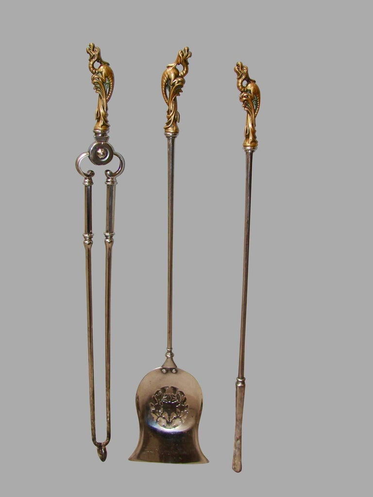 A fine quality set of English polished steel bronze handled fire tools of large size consisting of a poker, shovel and tongs, each tool with a fanciful bronze handle in the form of a mythological creature, circa 1840.