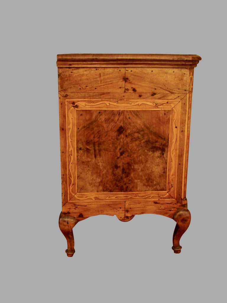 A charming Italian inlaid walnut three-drawer miniature chest, the top with a central star inlay, the drawer fronts and burled sides line inlaid with scrolls, supported by short cabriole legs.