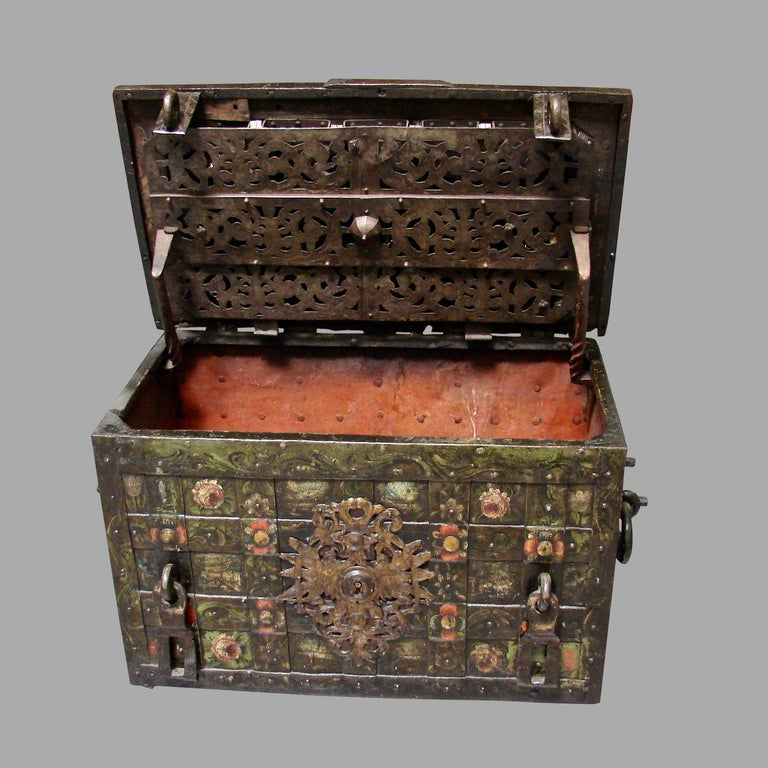 An impressive late 17th century Nuremberg wrought iron painted armada chest opening to reveal an elaborate working lock mechanism covered by an engraved pierced steel screen, the sides with twisted rope form iron carrying handles, circa 1650, shown