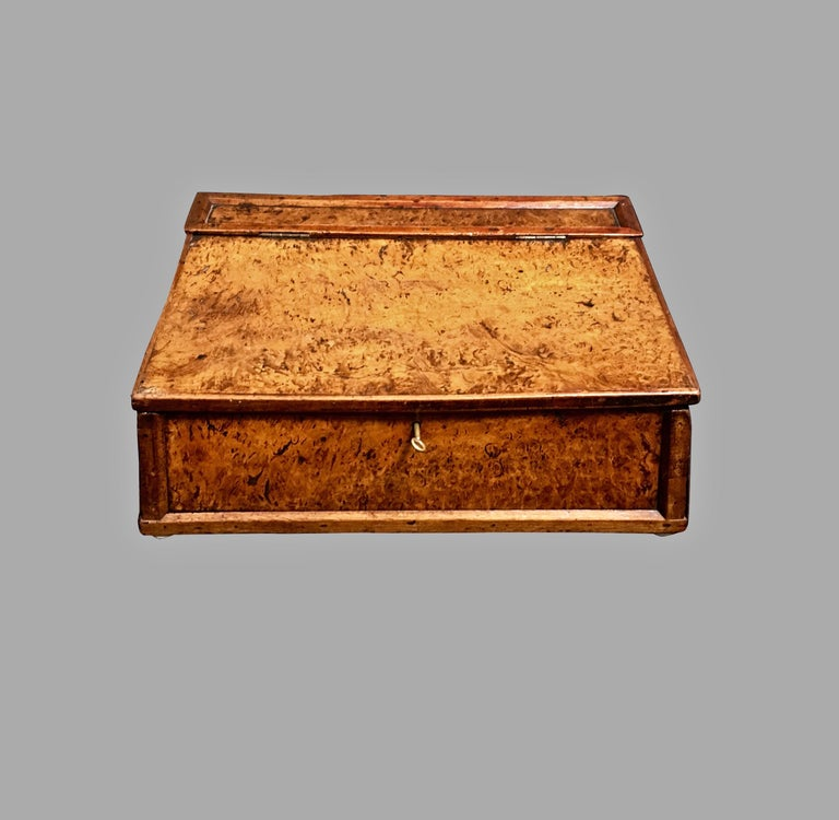 An English provincial burl elm writing slope, with a hinged lid opening to reveal a lined interior, circa 1800, with key.