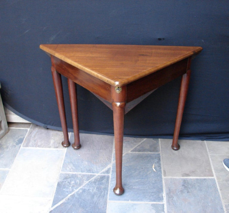 A George II mahogany corner envelope table with locking well, the square hinged top above a shaped frieze with gateleg support resting on shaped legs with pad feet, circa 1760.