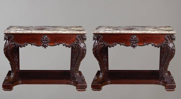 A rare pair of Chinese export hardwood console tables, each with a rectangular marble top above a carved frieze on cabriole supports raised on a platform. (For a similar single table, see Sotheby's