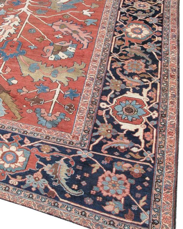 Although it is centered around a small rosette drawn within a deep indigo octagon, this long Serapi Heriz carpet nevertheless conveys the freedom and elegance of an all-over design type. Leaves and foliage are drawn in soft blues against a madder