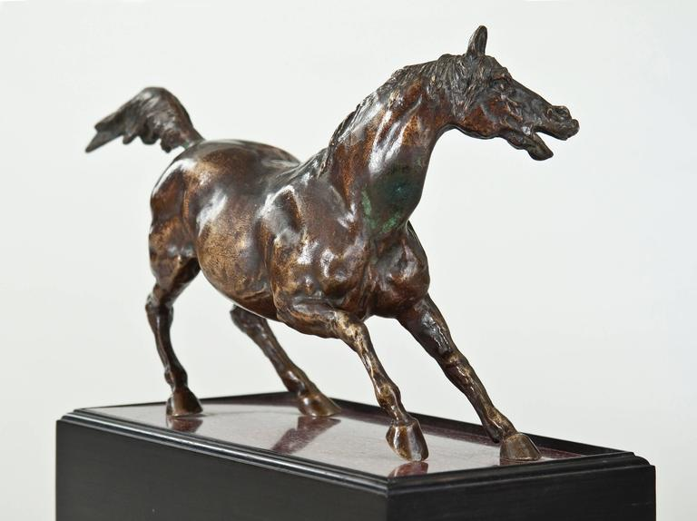 With a rich golden patina, the ears alert, mouth open and head turned, the front legs forward and rear legs angled, the tail erect, resting on a slab of Egyptian porphyry set within a ebonized wooden rectangular pedestal with a molded base.