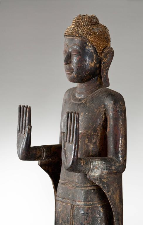 "Thai Painted and Parcel Gilt Wooden Standing Buddha  The standing Buddha with hands in the position of Abhaya mudrā conveying protection, peace, benevolence, and dispelling of fear.  Overall height 69"" Later base 10"""