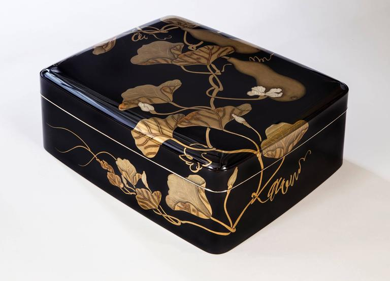 An exceptional box of the highest quality lacquer and of a striking modern design. The rectangular top with rounded corners depicting flowering and fruiting double gourd vines in hiramaki-e, takamaki-e, togidashi and nashiji, the interior depicting