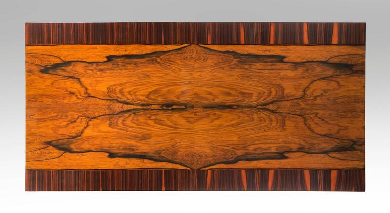 Wonderful robustly contrasting veneers enliven this table. The rectangular bookmatched palisander top crossbanded with macassar ebony, raised on ebonized fluted columnar legs headed by foliate capitals. Stamped: R within a triangle (for Reiners