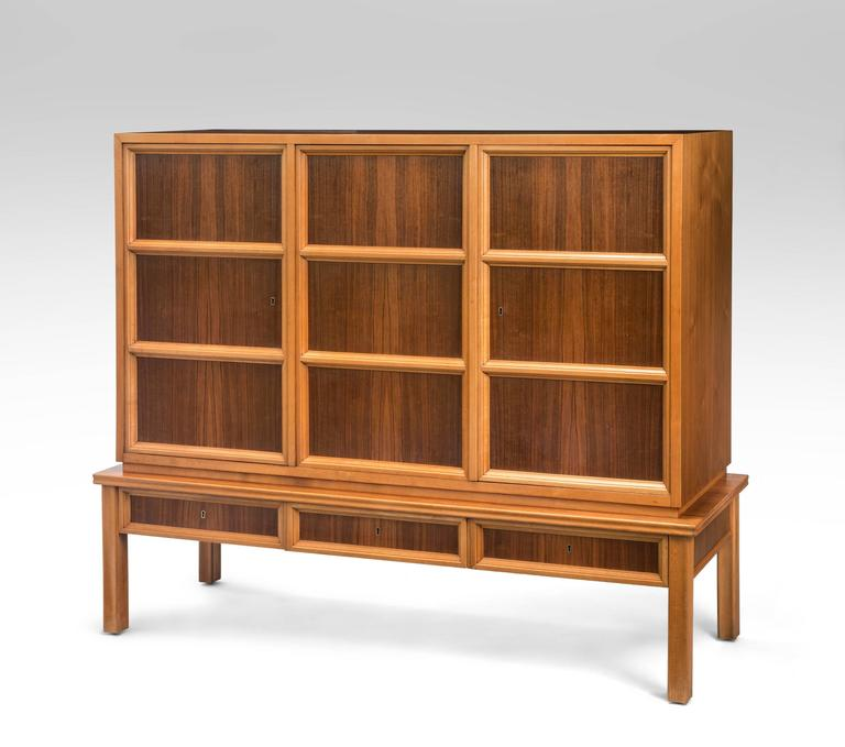 A very handsome cabinet composed of beautifully figured dark walnut framed by light color beech. The rectangular top, above a three door cabinet, each door adorned in molding against a rosewood background, above a three drawer lower frieze, the