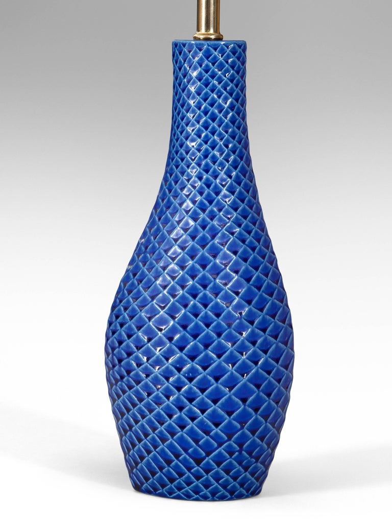 Each lamp with an elliptical mouth above a conforming neck and slightly asymmetrical swollen base, adorned in parallel scoring creating a scale-like pattern. A wonderful intense blue glaze.