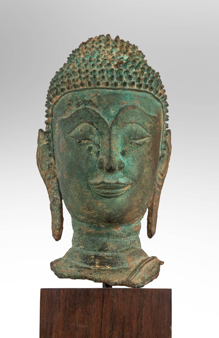 A Thai Verdigris bronze Buddha head Late Ayutthaya style in verdigris patinated bronze, the bust on a later stand. Ketumala missing. 17th century or later.