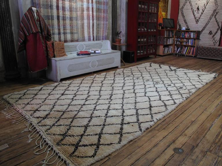 A massive Moroccan Berber carpet by the Beni Ouarain tribes of the NE Middle Atlas Mountains. The classical diamond grid, executed in small scale is dramatically interrupted at the top. A heavy, sturdy piece that was originally used as a comfortable