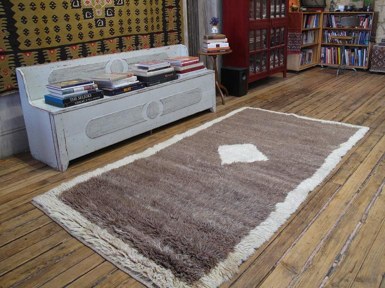 """A lovely old village rug from Central Turkey, woven with natural brown wool, in shaggy """"tulu"""" style. The minimalist design features a diamond in the center and a frame of wool in natural ivory tone. Simple rugs like these were made originally to be"""