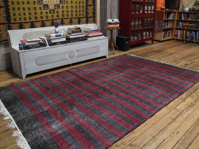 Banded goat hair Kilim rug. A primitive, dramatic tribal flat-weave rug woven entirely with goat hair in natural dark brown (almost black) and red bands. Woven as a utilitarian floor cover or rug, it has a rough texture. Rug has great