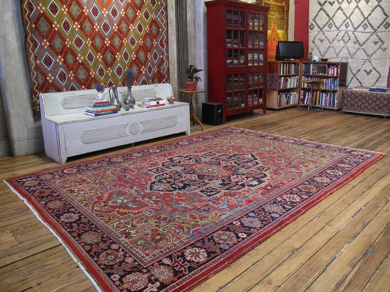 Antique Heriz carpet or rug with gentle wear. A very nice example of large format carpet weaving from the very prolific Heriz-Serapi region of Northwestern Iran, with a well-articulated design and natural dyes, indicating good age. The carpet has