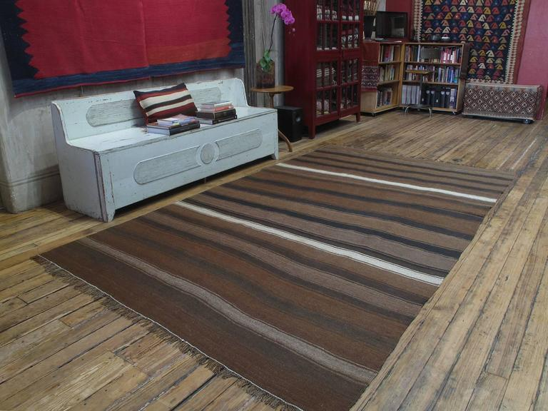 Kilim rug with wavy bands. A very nice old tribal Kilim rug from Southeastern Turkey, woven entirely with local hand-spun wool in rich natural tones of brown and ivory. Heavy and sturdy as it was meant for everyday use. Very well preserved rug.