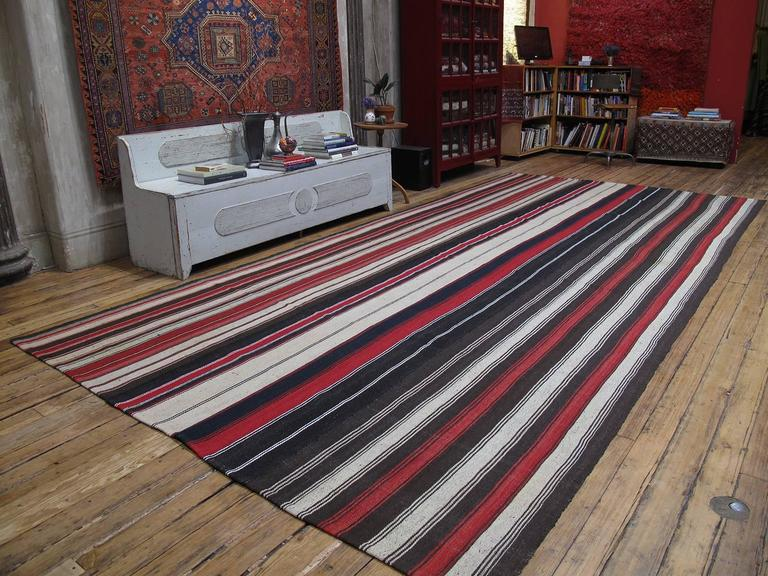 A large tribal floor cover, woven with goat hair and wool in natural tones and red stripes. Very high quality weaving in excellent condition. (Size can be adjusted. Please inquire).