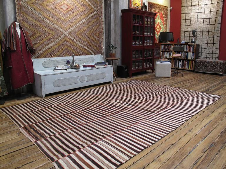 An old tribal flat-weave from Northern Iran, woven in five panels on a narrow loom with alternating bands of un-dyed ivory and brown and colorful stripes. A really nice and older example in very good state of preservation.  Since it is a fine