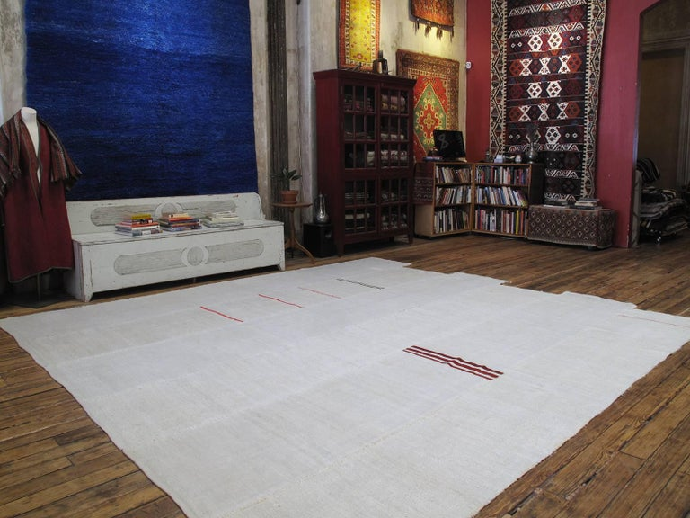 A very large kilim from Central Turkey, woven in six narrow panels of uneven length, with a few random colorful stripes. Such kilims were used in the fields to dry fruits, etc. during harvest time. Un-dyed jute (burlap) has turned white and became