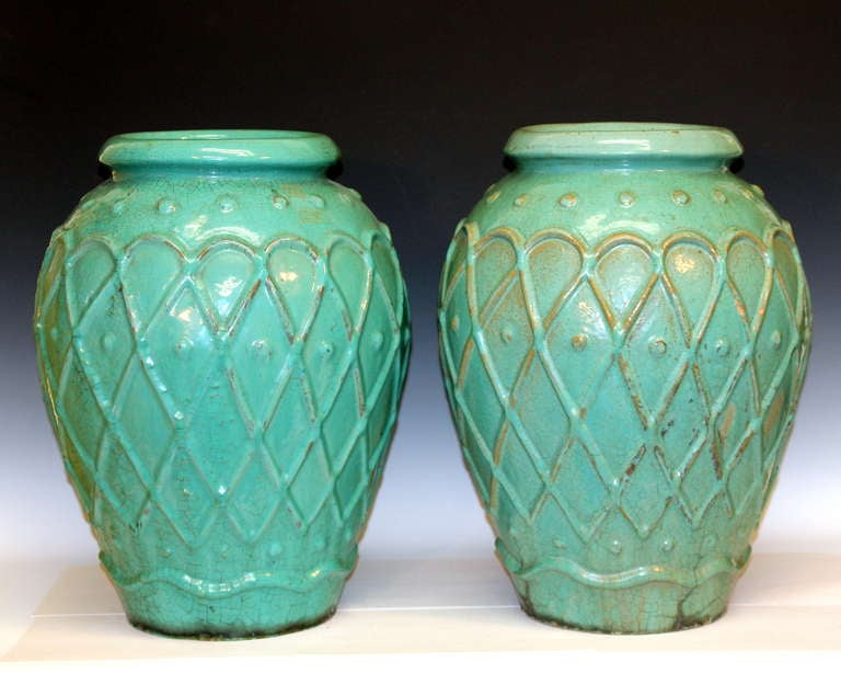 Large pair of garden urns by the Galloway Terracotta Company of Philadelphia in green/turquoise crackle glaze, circa early 20th century. One with impressed mark inside mouth rim. Measures: 20