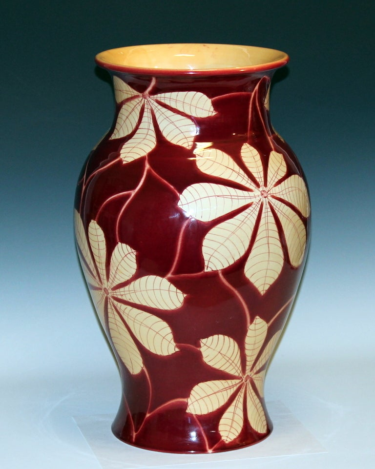 Large vintage hand-turned Italian pottery vase by Bellini for the Wannamaker's department store, circa 1970s. With exotic floral scroll on a deep oxblood ground. 19