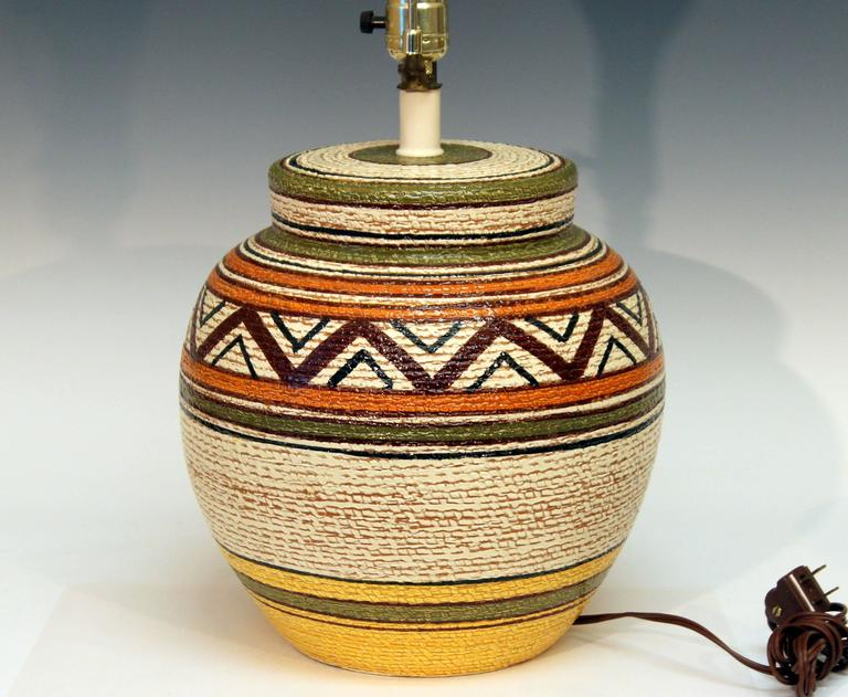 """Big, heavy, hand-turned, vintage Bitossi lamp with earth colored glazes in geometric pattern over a basket weave ground, circa 1970. Measures: 23"""" high overall, 13"""" to base of socket, pottery only is 11"""" high, 11"""" diameter. Shade"""
