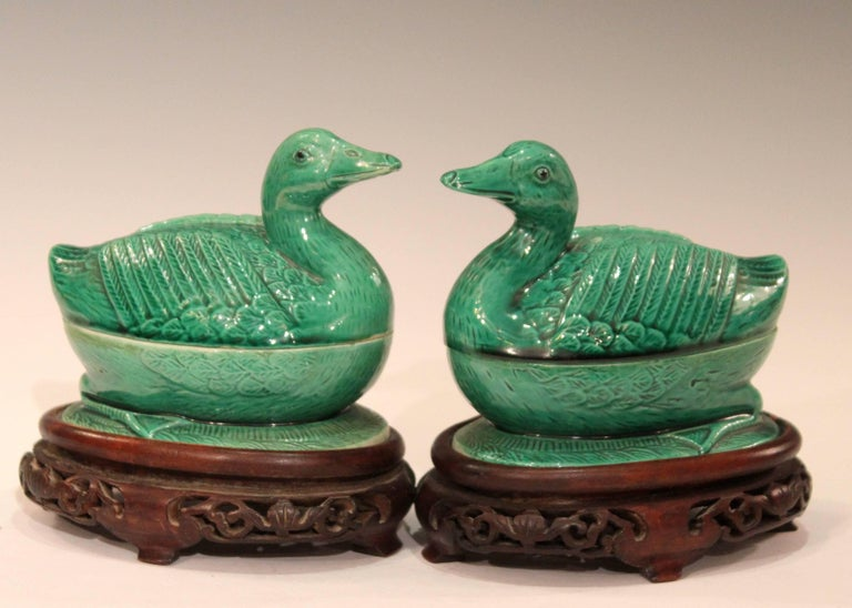Pair of old Chinese porcelain duck figure boxes on custom stands, circa early 20th century, Republican period. True pair with heads tilted in opposite directions and expertly rendered with sharp detail and great green crackle glaze. Measure: 5""
