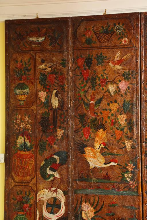 Very Fine English Six Panel Chinoiserie Decorated and Gilt Tooled Leather Screen, the center painted in vibrant original colors with birds and flowering branches with a border of symbolic antiques, all in imitation of a 17th century Chinese