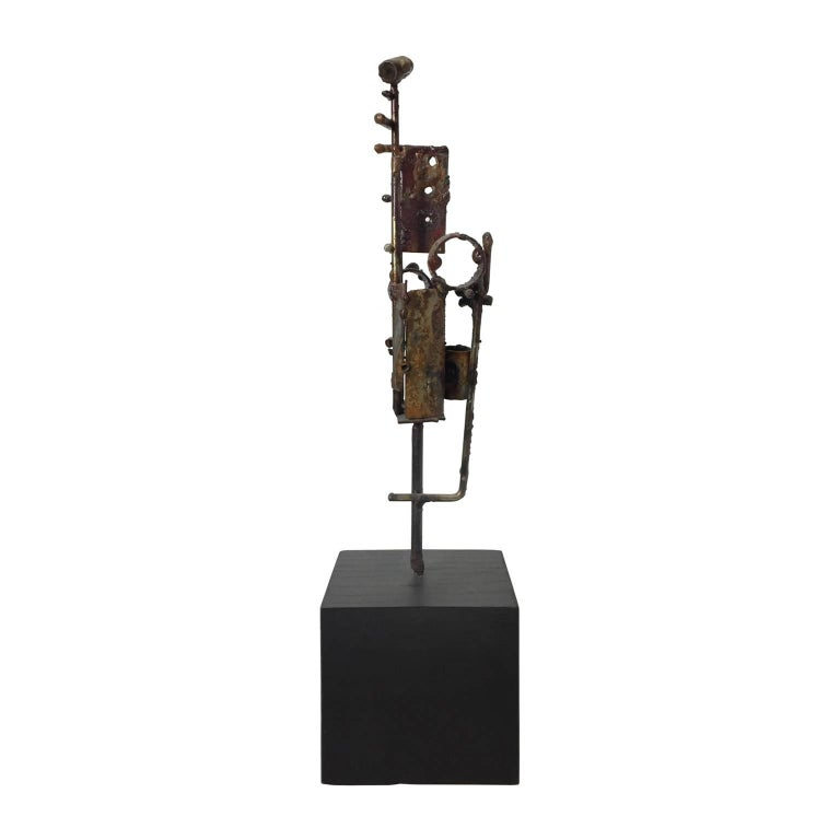 Brutalist welded metal sculpture on black wood base by R.E. Andermann. USA, 1972.